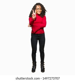 Young beautiful woman with curly hair wearing glasses smiling with happy face winking at the camera doing victory sign. Number two.