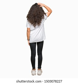 Young beautiful woman with curly hair wearing white t-shirt Backwards thinking about doubt with hand on head