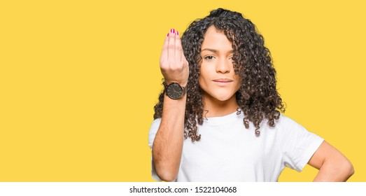 Young beautiful woman with curly hair wearing white t-shirt Doing Italian gesture with hand and fingers confident expression