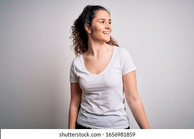 Young beautiful woman with curly hair wearing casual t-shirt standing over white background looking away to side with smile on face, natural expression. Laughing confident.