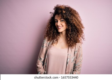 Young beautiful woman with curly hair and piercing wearing casual pink t-shirt with a happy and cool smile on face. Lucky person.