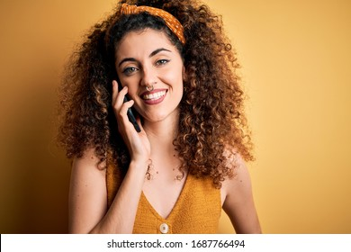 Young beautiful woman with curly hair and piercing having conversation talking on smartphone with a happy face standing and smiling with a confident smile showing teeth