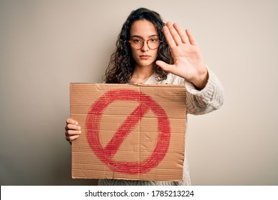 Young beautiful woman with curly hair holding banner with prohibited signal message with open hand doing stop sign with serious and confident expression, defense gesture