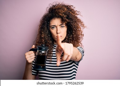 Young beautiful woman with curly hair and piercing doing coffee holding french coffeemaker pointing with finger to the camera and to you, hand sign, positive and confident gesture from the front