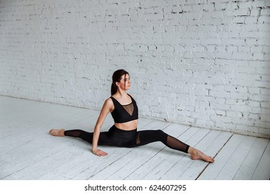 young beautiful woman dancer in a black leotard, sitting in splits on white brick background