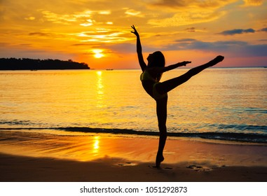 The young beautiful woman dances the ballet on the seashore at sunset