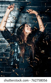 Young beautiful woman dancing in confetti and enjoying party. Happiness. New year, Birthday, Holiday Event concept