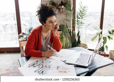 Young beautiful woman with dark curly hair sitting at the table with laptop and fashion sketches dreamily looking aside spending time in modern cozy workshop with big windows