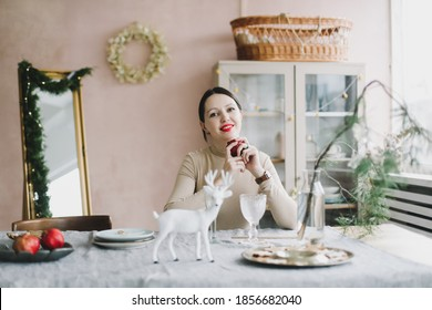 A young beautiful woman with dark hair in decorated for Christmas interior. Girl sitting at festive table setting with rustic decorations for Christmas and New Year.