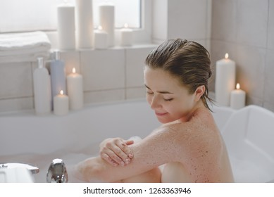 A young beautiful woman with dark short hair uses a body srab in a hot bath full of fragrant foam.