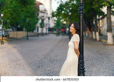 Young beautiful woman, dark-haired, stands with her back against the phonor in the street in the city center on a sunny day, in a white dress with a street in the background. Outdoor portrait.