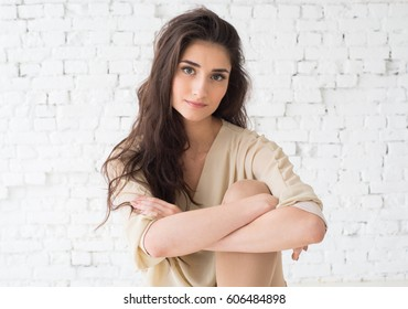 Young beautiful woman day light natural face portrait over brick wall