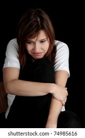 Young beautiful woman with depression isolated on black