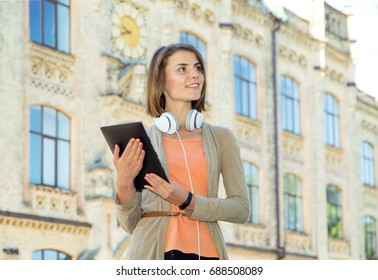 Young beautiful woman with digital tablet in hands and headphones. Smiling face.