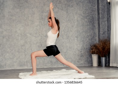 Young beautiful woman do yoga exercise on carpet at home living room. Healthy lifestyle and relaxation.