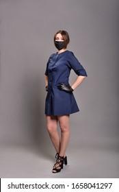 Junge schöne Frau Doktorin in schwarzer Schutzmaske und sexy Outfit auf grauem Hintergrund