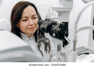 Young beautiful woman doctor - eye specialist - optometrist in an ophthalmologic clinic examines a patient with microscopy.
