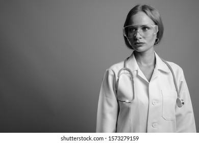 Young beautiful woman doctor as scientist wearing protective glasses in black and white