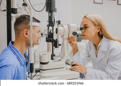 2194d4f389d Young beautiful woman doctor eye specialist optometrist in an  ophthalmologic clinic examines a patient