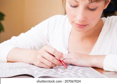 Young  beautiful woman doing crosswords in room
