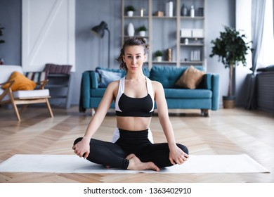 Young beautiful woman doing exercises in the living room at home. Sport and lifestyle concept.