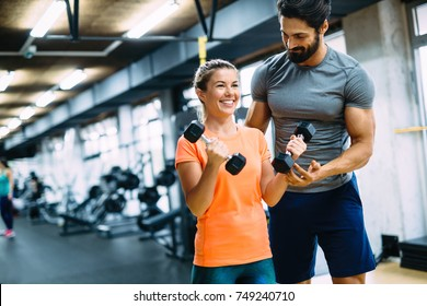 Young beautiful woman doing exercises with personal trainer