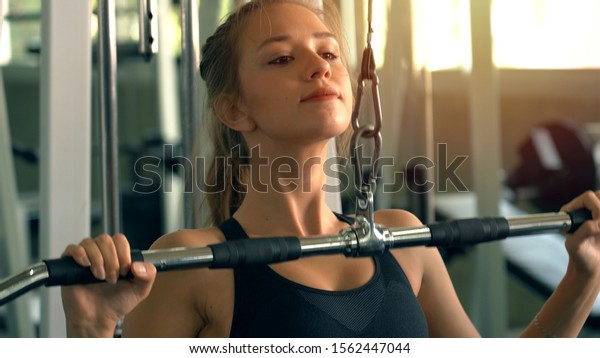 Young beautiful woman doing exercises with weight training in gym
