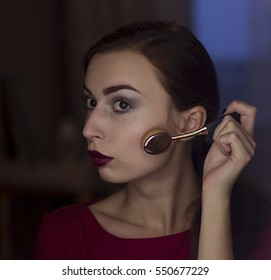 Young beautiful woman doing her make up oval brushes n a mirror with a ring light