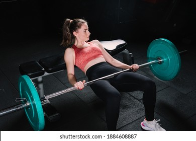 Young beautiful woman doing hip thrust. She poses with barbells in the gym.