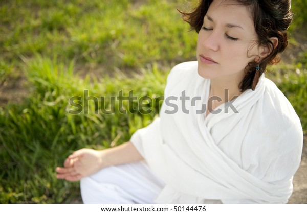 Young beautiful woman doing meditation in rice field.