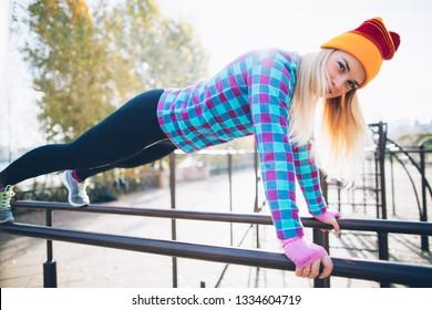 Young beautiful woman doing push ups on parallel bars at calisthenics park, looking at the camera