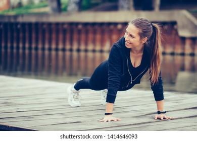 Young beautiful woman doing push up before running in urban training workout.