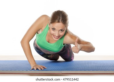 young beautiful woman doing push-ups and showing thumbs up