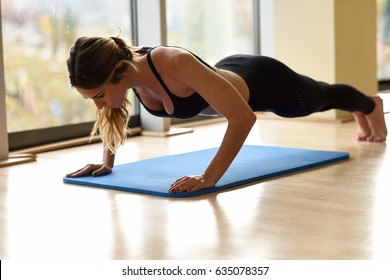 Young beautiful woman doing pushups in the gym on blue mat. Girl wearing sportwears clothes.