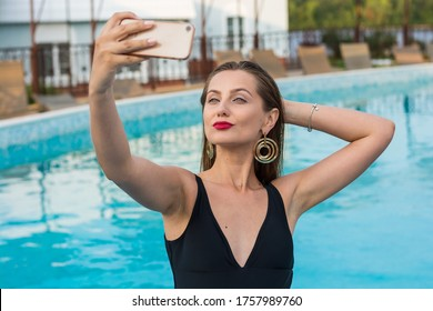 Young beautiful woman doing selfie on a smartphone in the pool. Beautiful young woman sits in the pool. Young sexy woman in the black swimsuit