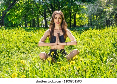 Young, beautiful woman doing sports exercises in a Sunny meadow in the Park