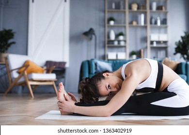 Young beautiful woman doing stretching exercises in the living room at home. Sport and lifestyle concept.