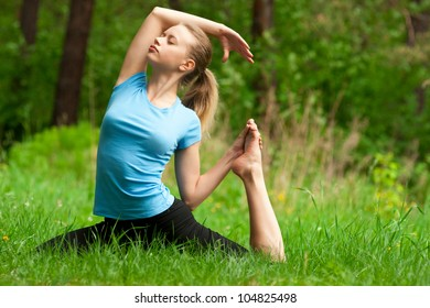 Young beautiful woman doing yoga meditation in forest outdoors