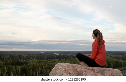 Young beautiful woman doing yoga and mindfulness exercises, while sitting on the edge of a hill and staring to the sunset horizon.