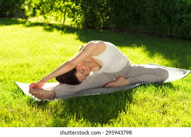 Young beautiful woman doing yoga in the park in the morning