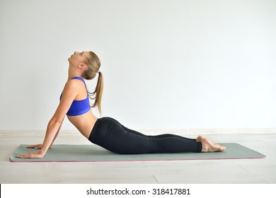 Young beautiful woman doing yoga poses indoor on grey background. Girl practicing her body in gym.