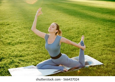 Young beautiful woman doing yoga exercises in park