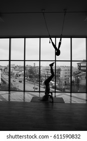 Young beautiful woman doing yoga on the background of the window