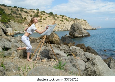 The young beautiful woman draws a picture