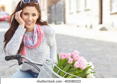 Young beautiful woman dressed in pastel on bicycle, pink and white tulips in a basket, spring outdoor.