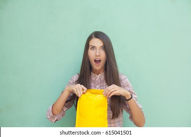 Young beautiful woman is dressed in a shirt in a cage, holds a yellow envelope in her hand, opens the parcel. Against the background of a blue, turquoise wall