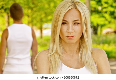 Young beautiful woman dressed in white hurt another, against green of summer park.
