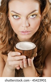 Young beautiful woman drinking coconut milk