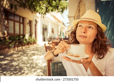 Young beautiful woman drinking coffee in summer cafe outdoors