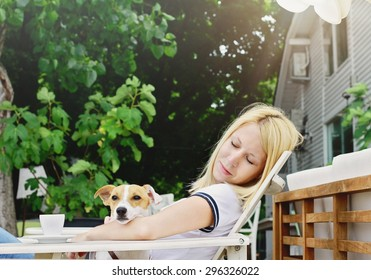 Young beautiful woman drinking a coffee sitting outside in a Rustic Chic cafe with her dog jack russell terrier